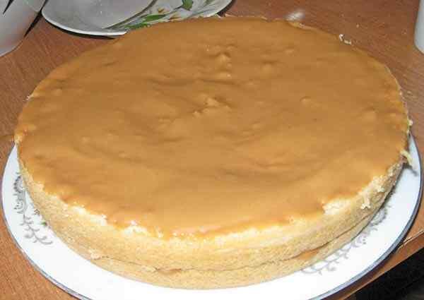 Разделяем бисквит для торта со сгущенкой на три слоя и промазываем их кремом